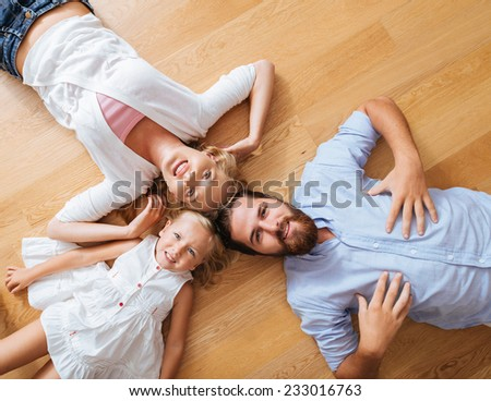 Littler girl and her parents lying on the floor in circle, view from above - stock photo