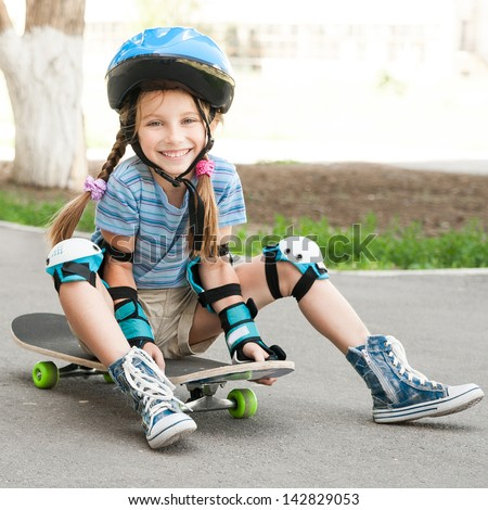 littlesmiling  girl with a helmet sitting on a skateboard - stock photo