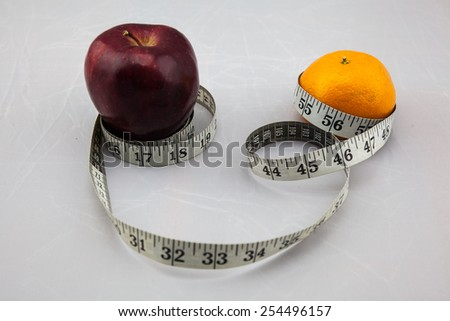 Live a Healthy Life - Red Apple And Orange with Measure Tape on Isolated White Background - stock photo