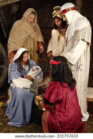 Live Christmas nativity scene reenacted in a medieval barn - the baby is a doll - stock photo
