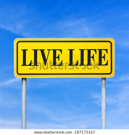 Live life written on yellow roadsign over blue sky. - stock photo