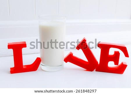 Live Love Milk - A glass of fresh milk within red letters spelling 'live' or 'love' - stock photo