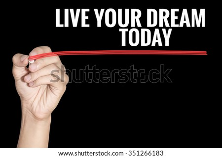 Live Your Dream Today word writing by men hand holding highlighter pen with line on dark background - stock photo