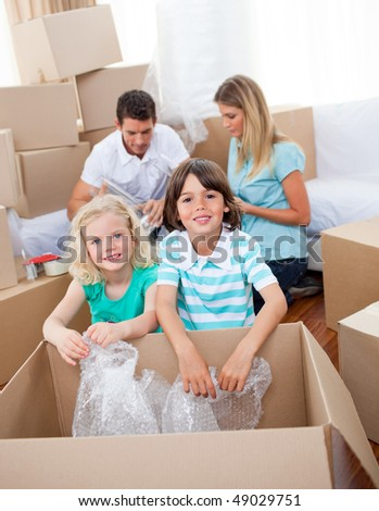 Lively family packing boxes while moving house - stock photo