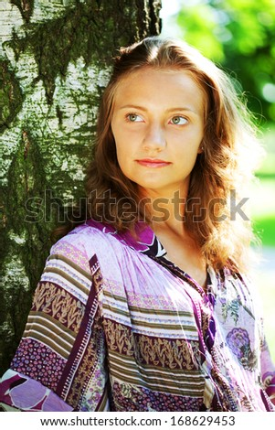 lively portrait of beautiful model in the park - stock photo
