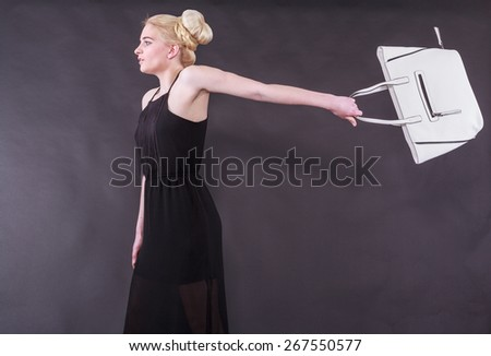 Lively young blond woman in a black dress with a white handbag on an outstretched arm back before black background, studio shot. /spirited young blond woman with purse - stock photo