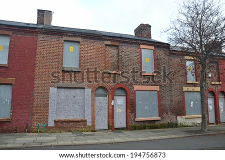 LIVERPOOL - December 10: derelict terraced houses in Toxteth, Liverpool, UK on December 10, 2013. The house with graffiti was the birthplace of Ringo Starr, drummer of The Beatles.  - stock photo