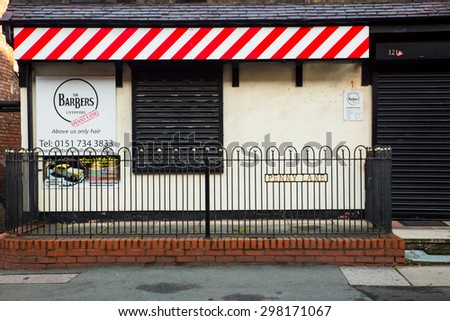 LIVERPOOL, UNITED KINGDOM - OCTOBER 12, 2014:  Landmark Penny Lane Barber Shop in Liverpool made famous by The Beatles in 1967.  - stock photo