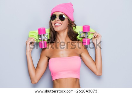 Living a colorful life. Attractive young woman in funky clothes carrying colorful skateboard on her shoulders and smiling while standing against grey background  - stock photo