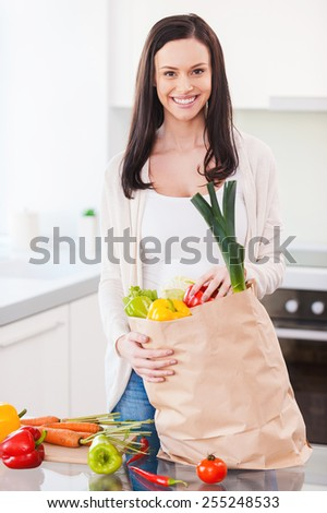 Living a healthy life. Beautiful young woman unpacking shopping bag full of fresh vegetables and smiling while standing in the kitchen - stock photo