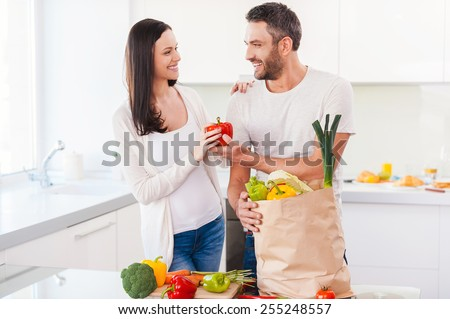 Living a healthy life together. Beautiful young couple unpacking shopping bag full of fresh vegetables and smiling while standing in the kitchen together - stock photo