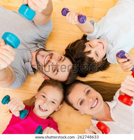 Living an active life. Top view of happy sporty family bonding to each other while lying on the floor and holding dumbbells - stock photo