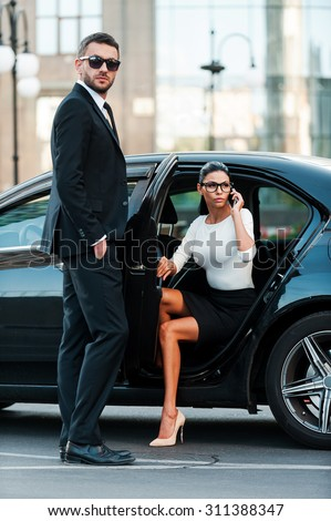 Living in a business world. Full length of confident young businesswoman coming out her car while her male colleague standing near and looking at camera - stock photo