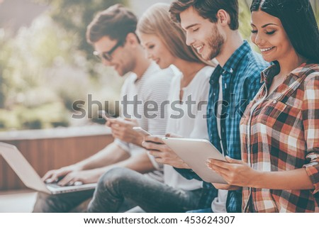 Living in digital age. Group of happy young people holding different digital devices and smiling while sitting in a row outdoors - stock photo