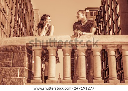 Living in harmony. Two friends standing by fence on street, facing each other, smiling, chatting in the front of neighborhood in a big city. Concept of relationship, communication between neighbors.  - stock photo