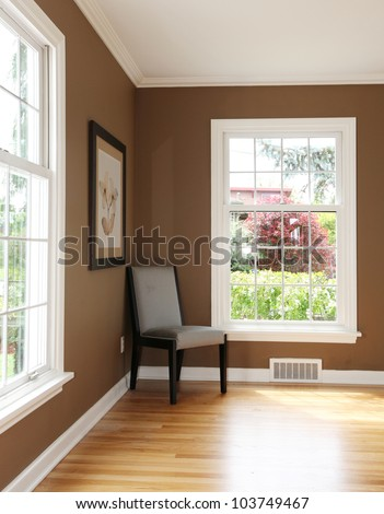 Living room corner with chair and two windows and hardwood floor. - stock photo