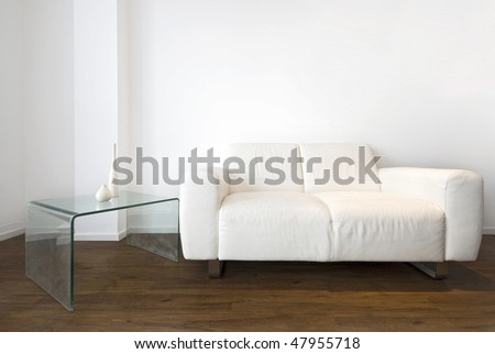 Living room detail with a white leather sofa and designes glass coffee table - stock photo