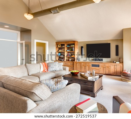 Living Room in New House: Large Furnished living Room in Luxury Home with Television, Couch, Coffee Table and Built-In - stock photo