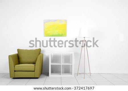Living room interior with green armchair, white shelf and lamp on white wall background - stock photo