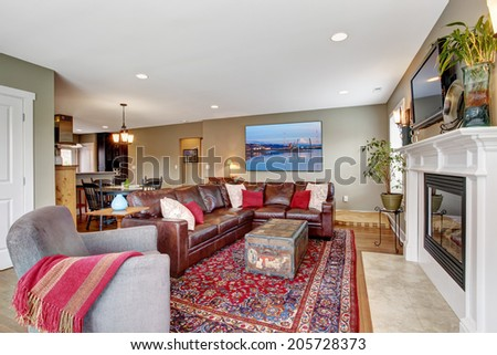 Living room interior with hardwood floor. View of burgundy leather couch and cozy fireplace with tv above it - stock photo