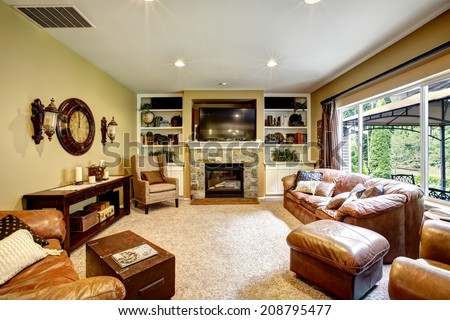 Living room interior with leather furniture set, stone fireplace and tv - stock photo