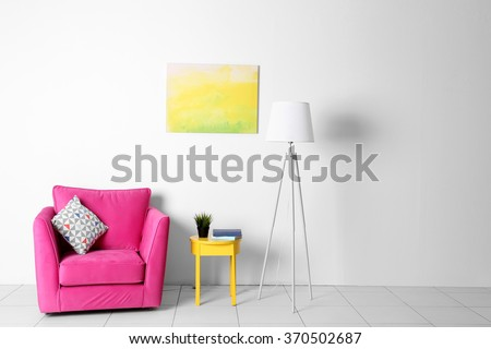 Living room interior with pink armchair, lamp and yellow chair  on white wall background - stock photo