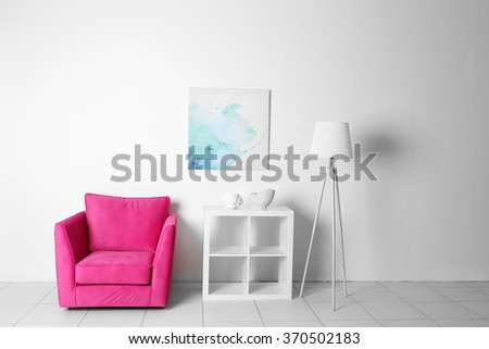 Living room interior with pink armchair, white shelf and lamp  on white wall background - stock photo