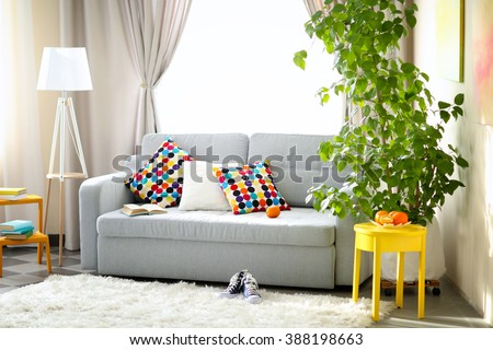 Living room interior with sofa, lamp and green tree - stock photo