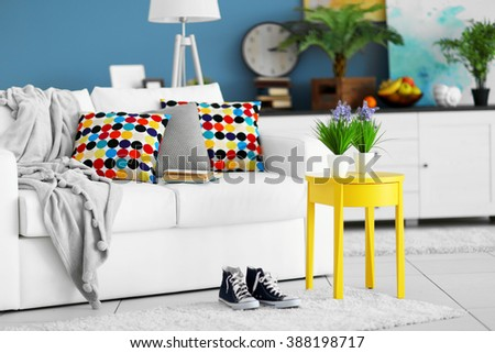 Living room interior with white furniture and green plants on blue wall background - stock photo