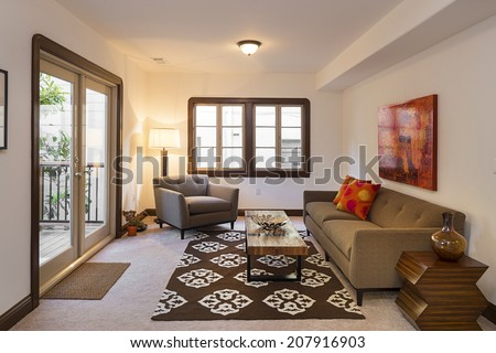 Living room of Mediterranean home with sliding french doors, armchair and table with wooden board. - stock photo