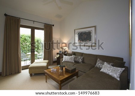 Living room with brown corner sofa and porch view - stock photo
