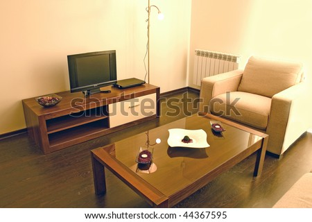 Living room with cosy sofa and arm chair, small table and DVD and TV set. - stock photo