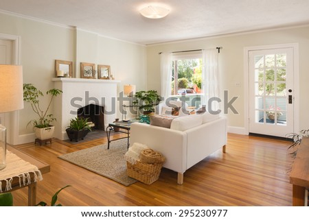 Living room with fire place in beige with wooden floor, handwoven rug and white couch.  - stock photo