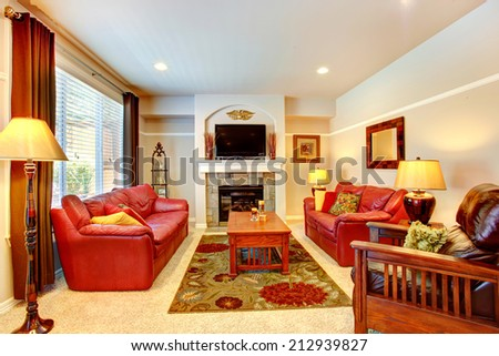 Living room with fireplace, red leather couches and TV in luxury house - stock photo