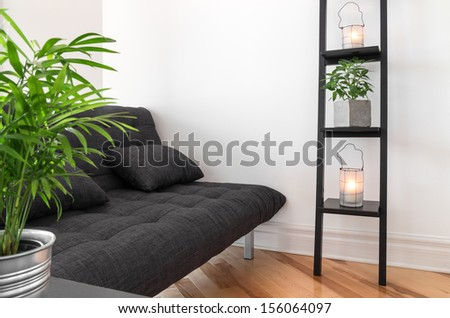 Living room with gray sofa, decorated with plants and lanterns. - stock photo