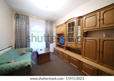Living room with green sofa, a wall cabinet and television set - stock photo
