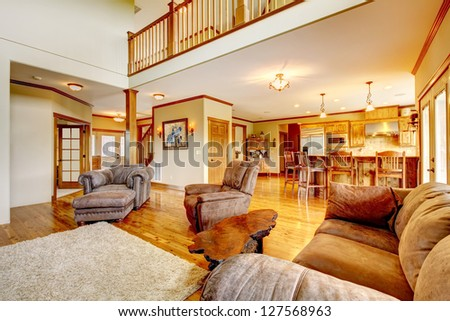 Living room with high ceiling, kitchen and leather sofa. - stock photo