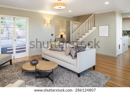 Living room with new wooden floor, staircase, couch and french doors. - stock photo
