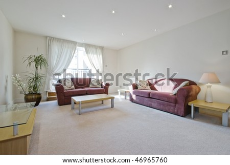 living room with purple sofas and massive plant with flowers - stock photo