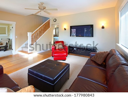 Living room with red leather chair, staircase and television - stock photo