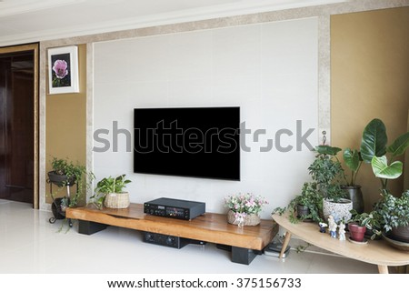 Living room with smart television(TV, LED, LCD, HD, Full HD, UHD, display), gold wall, white marble stone, wood table, audio, green plant pot, flower pot, picture. - stock photo