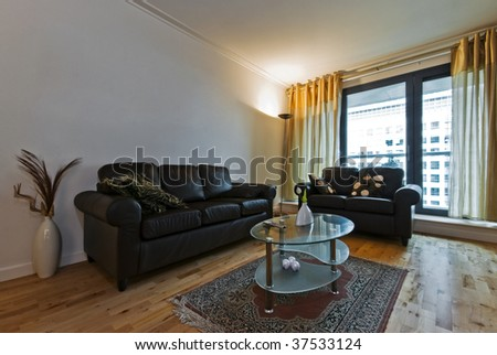 living room with wood imitation laminate floor and leather sofas - stock photo