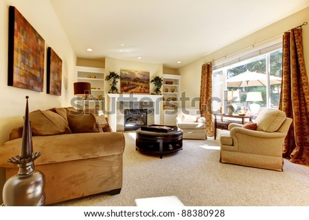 Living room with yellow, art, large window, sofas and fireplace. - stock photo