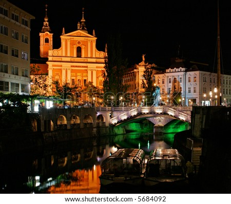 Ljubljana at night, with the Triple Bridge and Franciscan Church. - stock photo