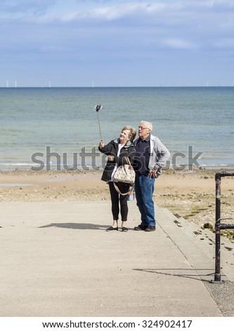 Llandudno, Wales, U.K- September 9, 2015: Elderly tourists taking selfies with digital camera on a selfie stick at Llandudno beach North Wales  - stock photo