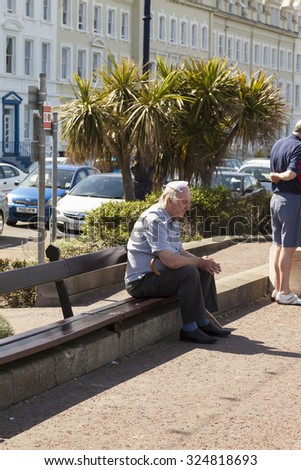 Llandudno, Wales, UK - May 17, 2014: Elderly man appears to be suffering from heat exhaustion protects his balding head with knotted handkerchief from the hot sunshine whilst sitting on wooden bench  - stock photo