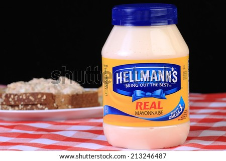 LLANO, TEXAS - AUGUST 26, 2014: Jar of Hellmann's Mayonnaise in front of sandwich on red country-style tablecloth. Hellmann's Mayonnaise has been sold publicly since 1905 and mass marketed since 1912. - stock photo