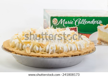 LLANO, TEXAS-Jan 05, 2015:   Made from scratch Marie Callender's Banana Cream Pie in aluminum pie pan with Packaging as background. - stock photo