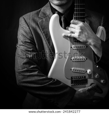 lo-key lighting image of male guitarist in grey suit hold & hug electric guitar on dark background - stock photo