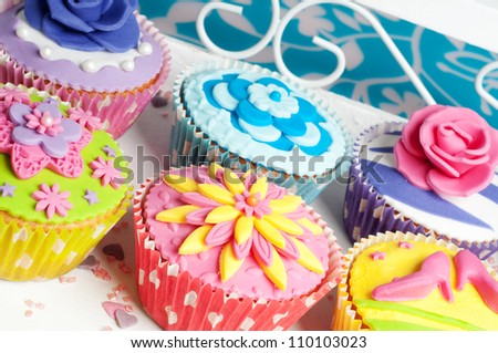 Load of cupcakes in different colors with flower decoration - stock photo